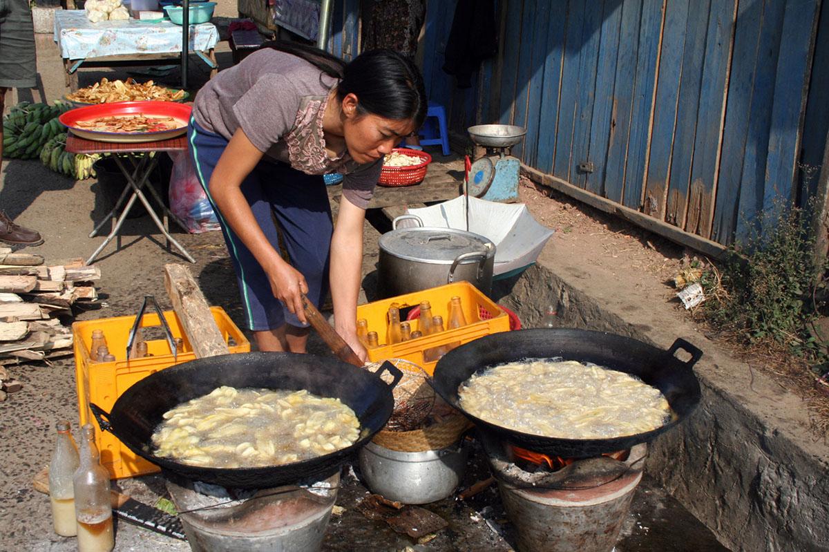 Vrouw bereidt eten op straat in Laos.