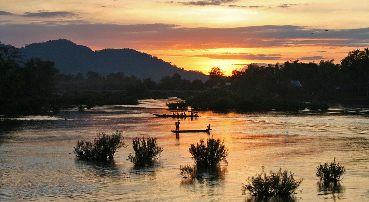Zonsondergang met boten op mekong bij si pan don in Laos.