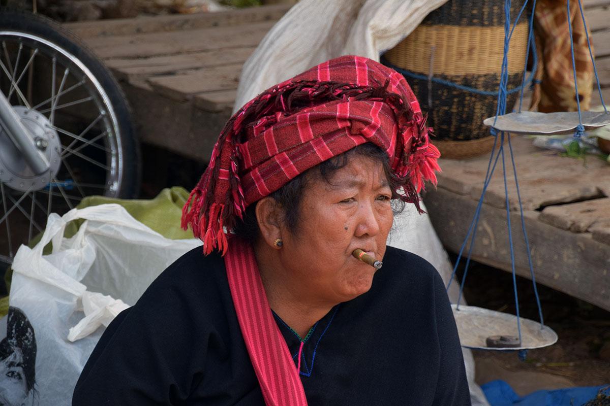 Traditionele vrouw met sigaar op markt bij het Inle Lake.