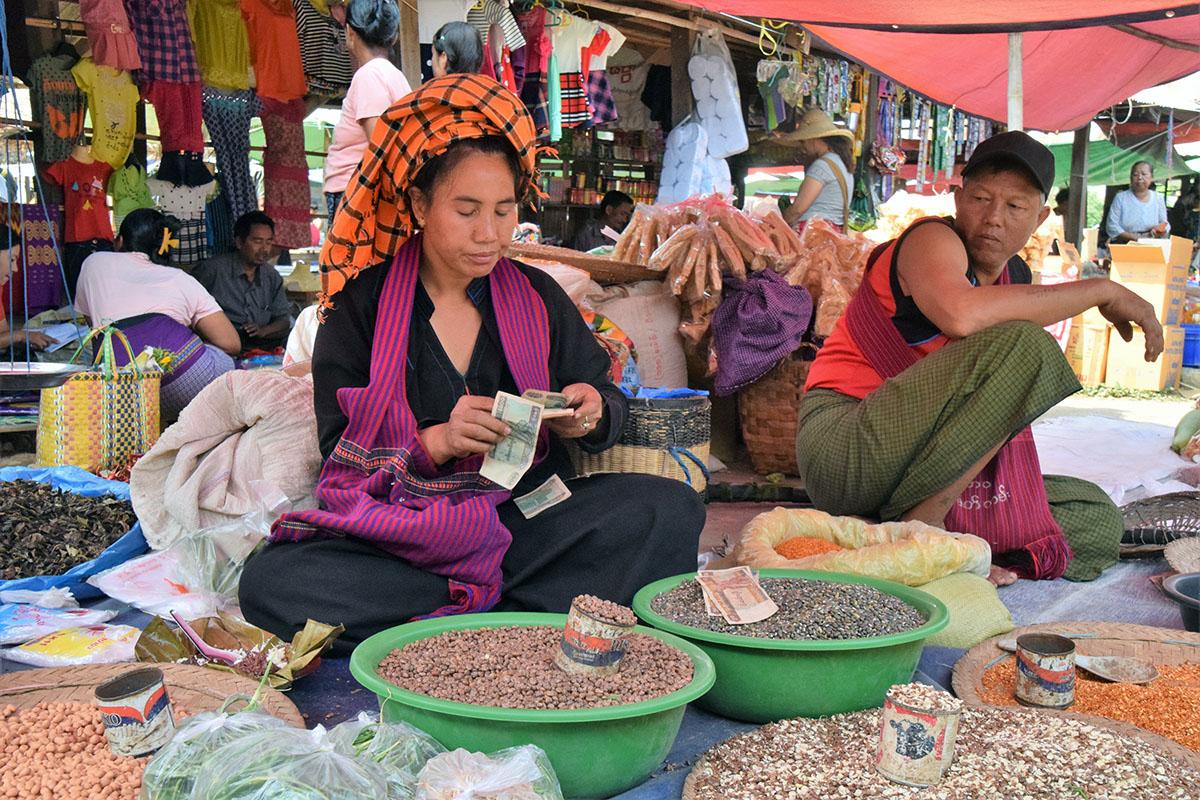 handelsvrouw op markt bij het Inle Lake telt haar geld.
