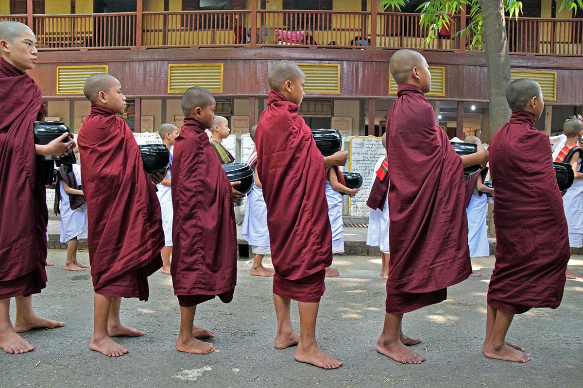 Jonge monniken met hun blote voeten bij mahagandayon monastery
