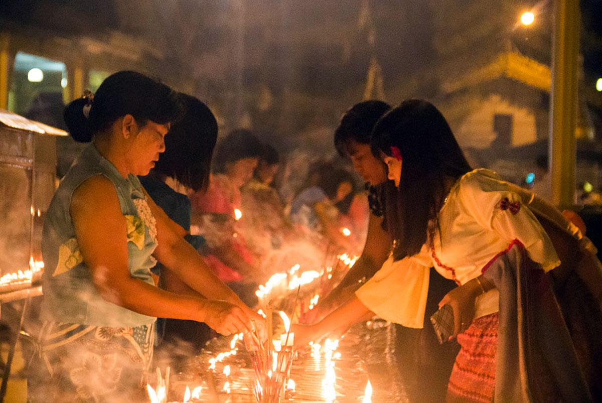Kaarsen aansteken bij de Shwedagon Paya.