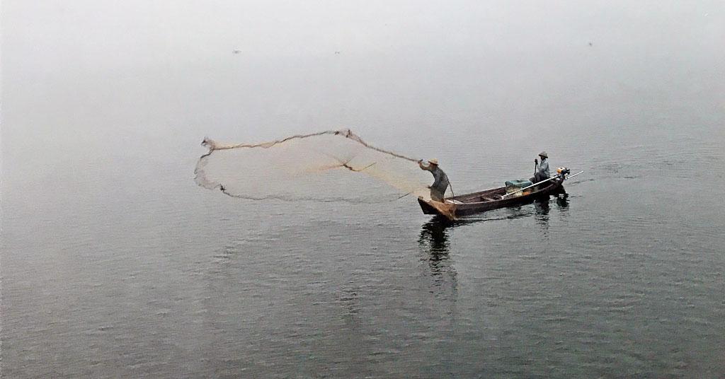 Visser werpt net uit op het meer bij de U-Bein Bridge.