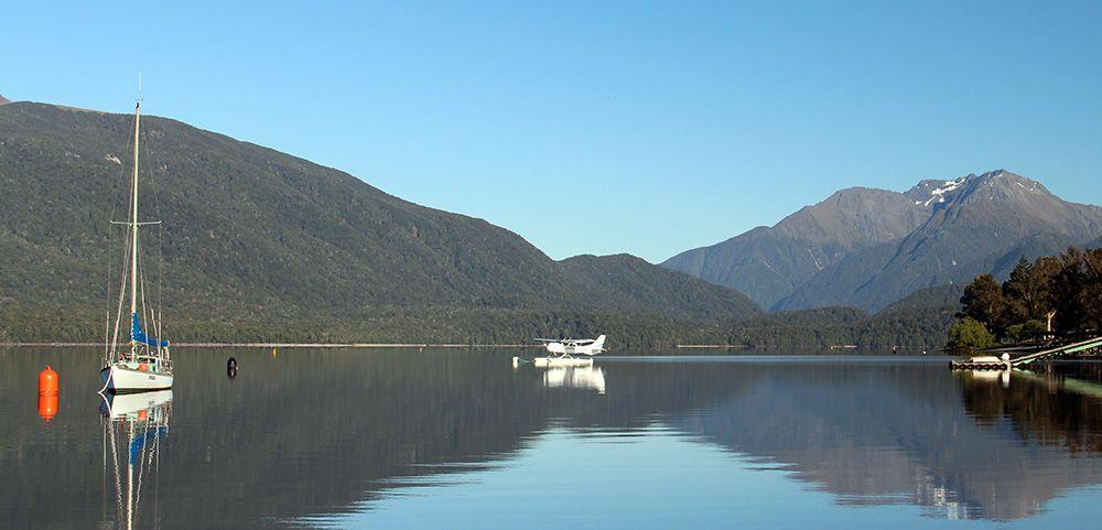 Watervliegtuig en zeiljacht op het Zuidereiland van Nieuw-Zeeland