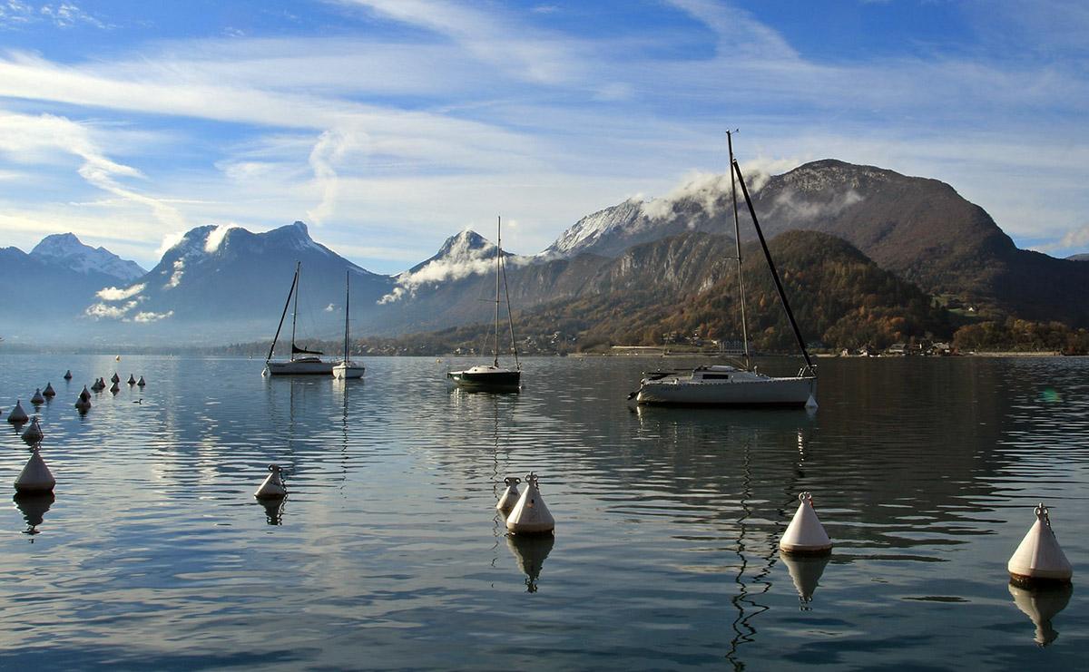 Boten op het meer van Annecy, omgeven door bergen.