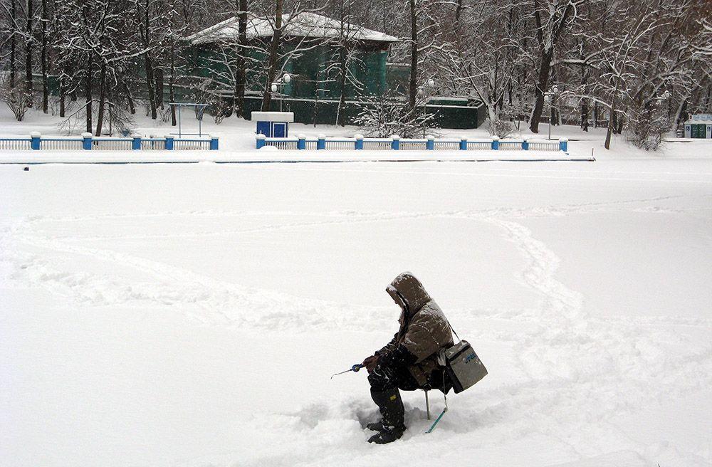 Visser op een dichtgevroren vijver in het centrum van Moskou in Rusland