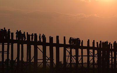 Over de U-Bein Bridge lopen bij zonsondergang