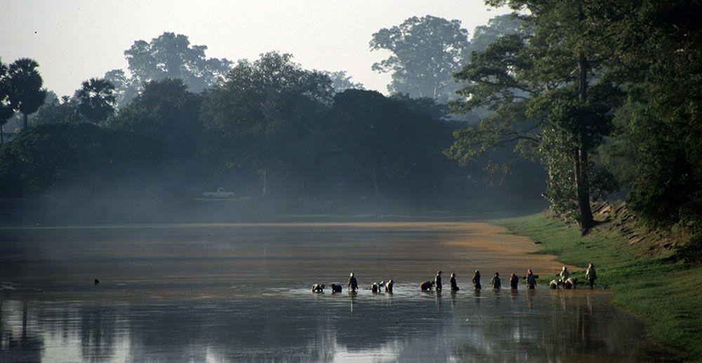 Lokale bevolking waadt door water bij Angkor Wat, hoofdattractie van Cambodja.