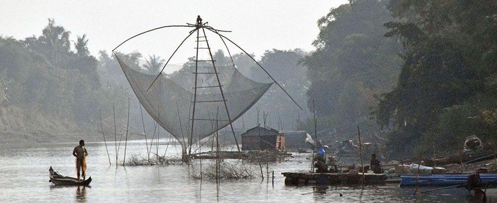 vissers met enorm visnet op rivier bij Siem Reap.