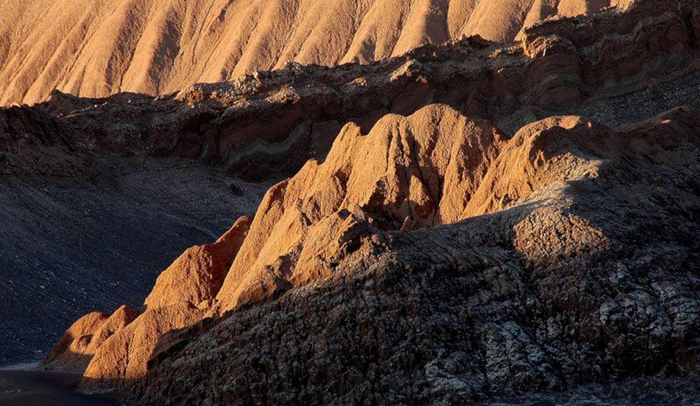 De zon kleurt de rotsen in Valle de la Luna.