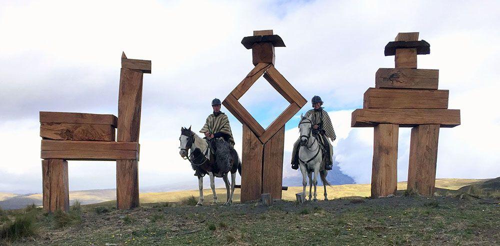 toeristen in traditionele kleding te paard bij monument Cotopaxi.
