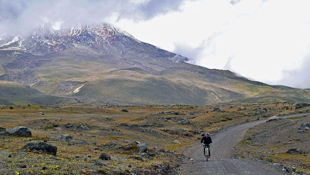 Mountainbiker met op de achtergrond de Cotopaxi vulkaan.