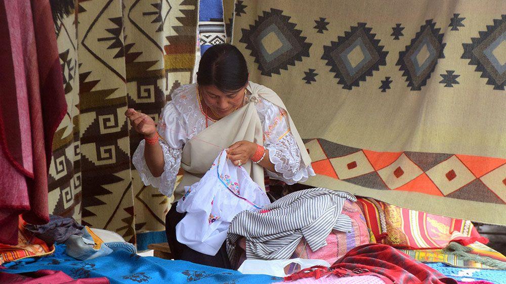 Vrouw borduurt op weekmarkt in Otavalo.