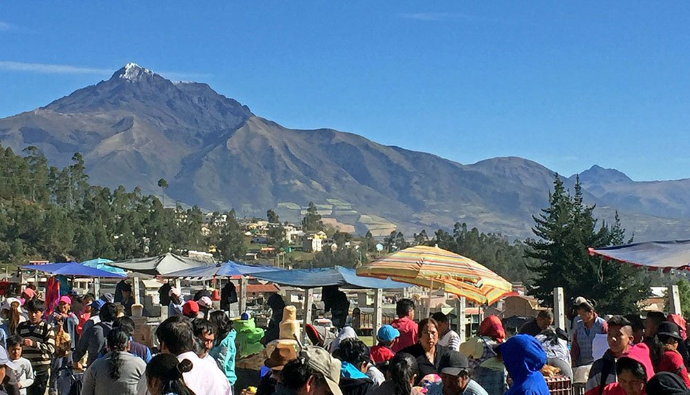 Mensen op markt in Otovalo met op de achtergrond een vulkaan.