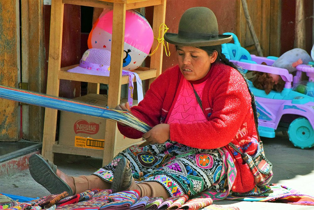 Vrouw op straat weeft kleurrijke doek