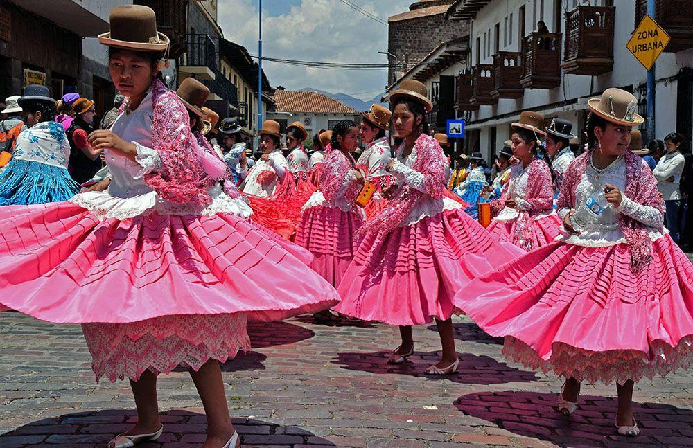 Kleurrijke straatparade met dansende vrouwen in Cuzco