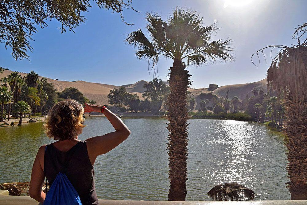 Toerist kijkt uit over het meertje in Huacachina
