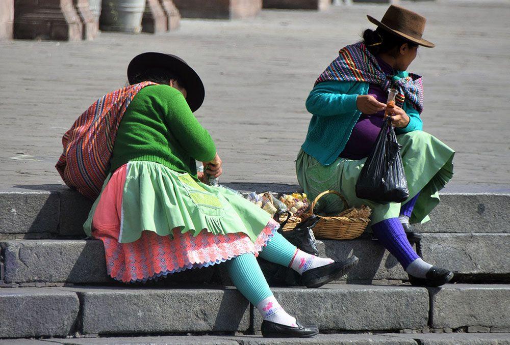 Kleurrijke vrouwen zitten op de stoep in Peru met hun handelswaar