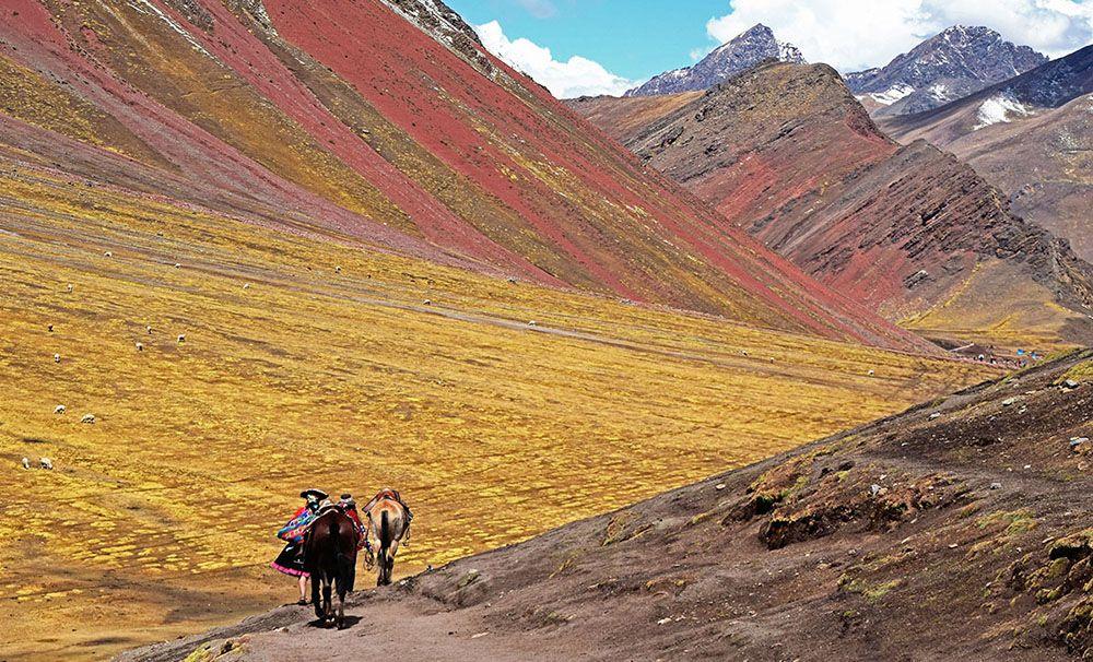 Peruaanse vrouw trekt met twee paarden door kleurrijk berglandschap
