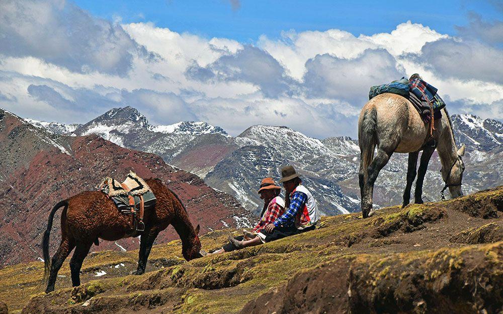 Peruaanse vrouwen met paard rusten uit bij Rainbow Mountain