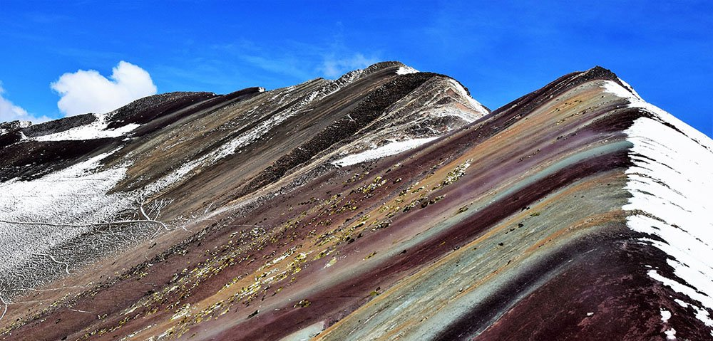 De Rainbow Mountain met aan een kant een besneeuwde helling