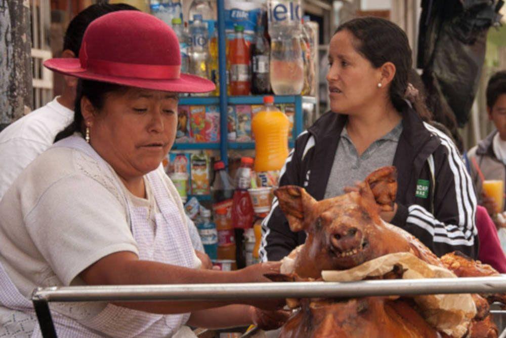 Een marktkoopvrouw verkoopt geroosterde varkens